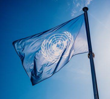 UN flag against blue sky.