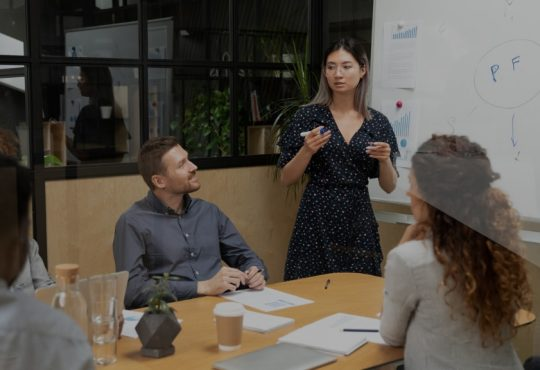 Woman giving presentation in front of colleagues in board room