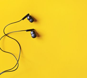 Black ear buds on yellow background