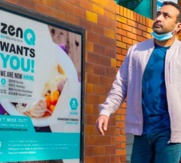 Man walks by business hiring ad.