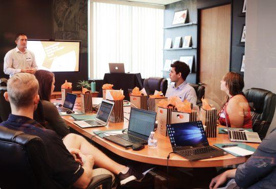 People sitting around boardroom table.
