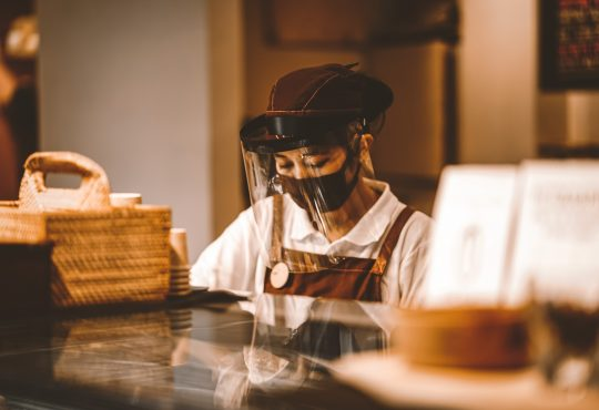 Woman wearing face shield working behind cafe counter.