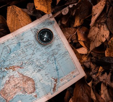 Map and compass on pile of leaves