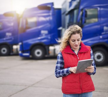 Truck driver looking at tablet while standing in front of parked transport trucks.
