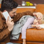 Father checking temperature of sick daughter lying on couch