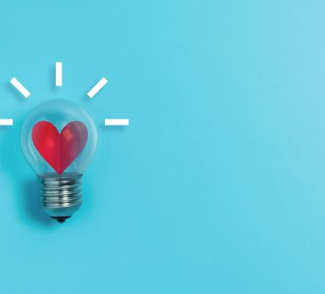 Red heart in light bulb on blue background