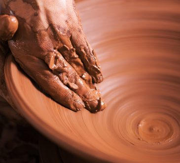 Potter working with clay on wheel.
