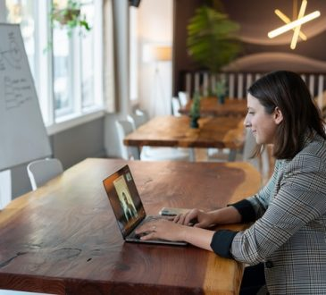 Woman sitting at desk taking video call.