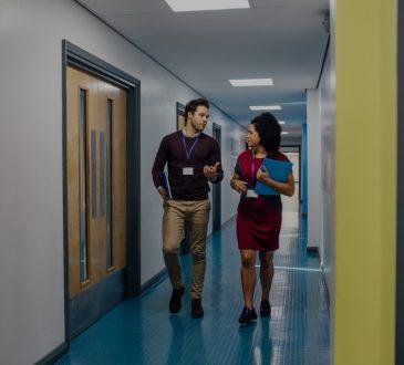 Man and woman walking down school hallway talking.