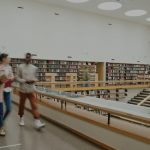 Students walking in college library.