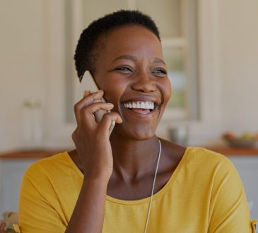 Woman smiling and talking on phone.